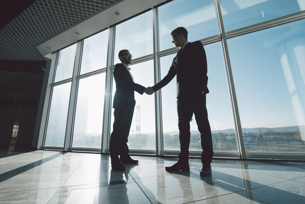 businessmen shaking hands in a commercial property